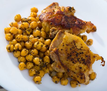 Baked chicken thighs served with spicy garbanzos on white plate