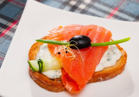 Slices of salmon and cucumber served on toasted baguette with cream sauce on white plate