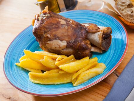Close up of delicious baked pork knuckle with potatoes, served  on  plate