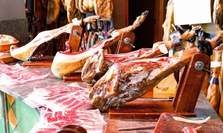 Legs of traditional Spanish jamon fixed on wooden jamoneras ready for sale in small shop