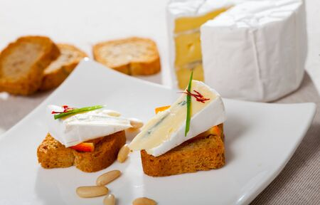 Close up image of canape with soft blue cheese and orange