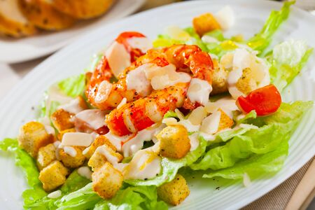 Tasty salad of fresh lettuce, spicy croutons, roasted shrimps and sliced ​​Parmesan cheese (Caesar salad)