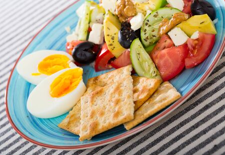 Vitamin salad with tomatoes, avocado, cucumber, feta cheese and walnuts served with boiled egg and crackers