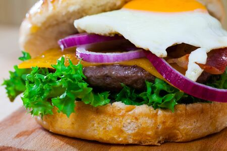 Image of hamburger with beef patty, cheese, fried egg and lettuce