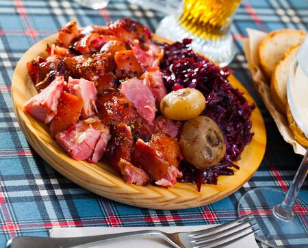 Juicy baked in beer chopped pork knuckle served with braised red cabbage Stock Photo