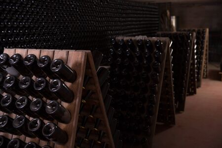 Wine aging in bottles on wooden racks in winery cellar