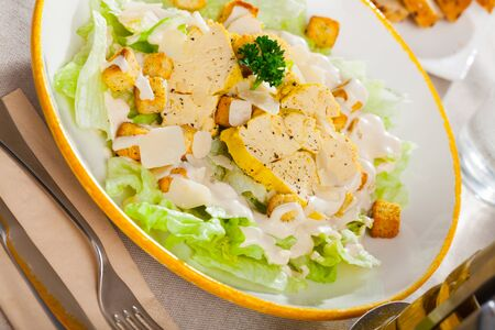 Delicious Caesar salad of romaine lettuce and croutons dressed with delicate sauce topped with chicken and Parmesan cheese