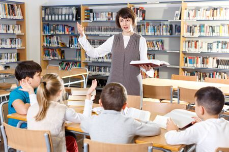 Friendly female teacher giving lesson to group of school kids in school library
