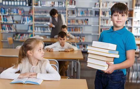 Portrait of happy tween boy standing in classroom with books in hands