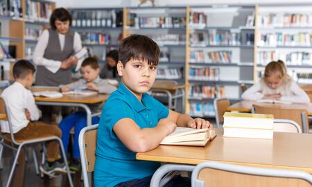 Portrait of diligent tween boy preparing for lesson in school library, reading textbooks