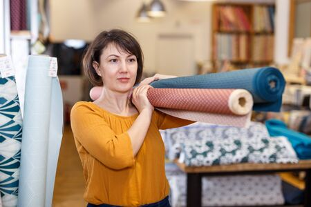 Experienced saleswoman arranging fabric bolts in textile shop, preparing for sale Stockfoto