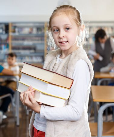 Portrait of smiling teen girl standing with pile of books in school library
