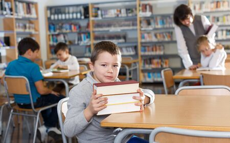 Smiling intelligent boy holding pile of books sitting at desk in modern school library