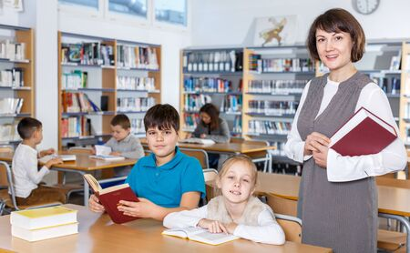 Portrait of young female librarian and diligent schoolkids during classes in school library
