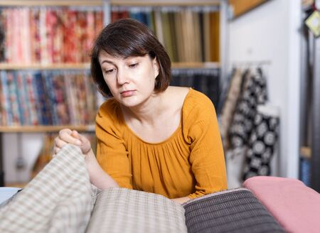 Pensive woman choosing textiles for dressmaking in fabric shop