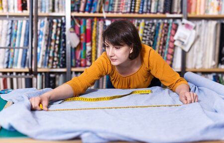 Focused saleswoman working in fabric store, measuring and cutting off piece of cloth to order