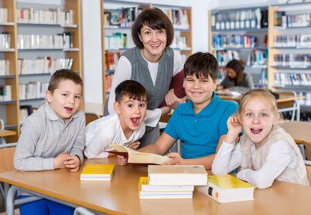 Porträt einer freundlich lächelnden Gruppe von Schülern mit einer Lehrerin, die in der Schulbibliothek sitzt Standard-Bild