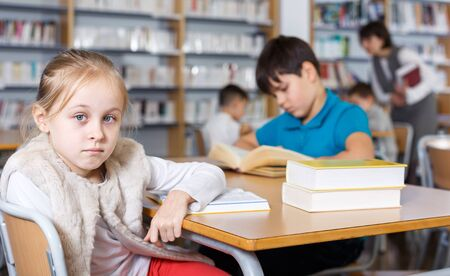 Portrait of cute preteen girl preparing for lesson in school library, reading textbooks