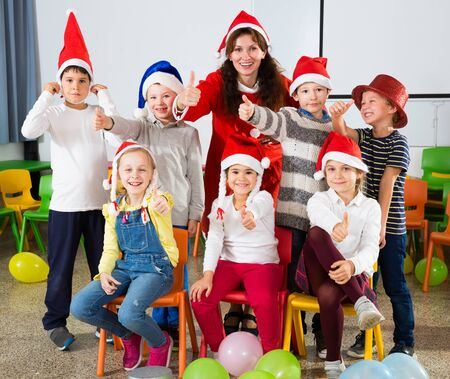 Group portrait of young female teacher and happy school children in Santa hats giving thumbs up together in classroom
