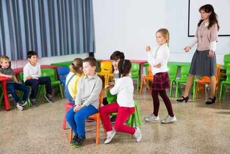 Happy kids and female teacher playing musical chairs together during break in classroom at elementary school