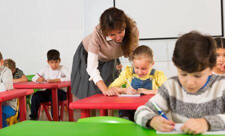 Friendly teacher woman helping children during lesson in schoolroom