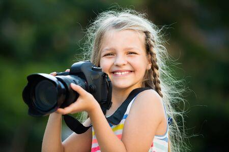 Positives weibliches Kind, das am Sommertag mit der Kamera im Park fotografiert Standard-Bild
