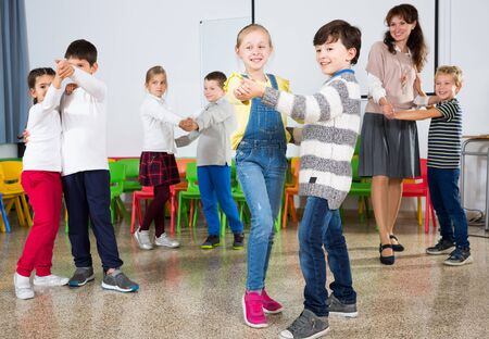 Happy kids and female teacher dancing together in classroom at elementary school