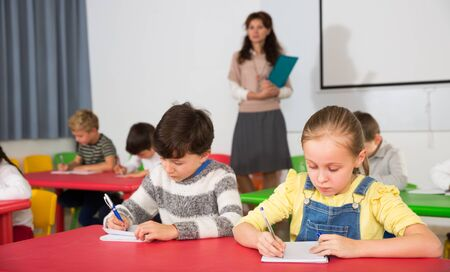 Portrait of diligent preteen students writing exercises at lessons with young female teacher in primary school Stock Photo
