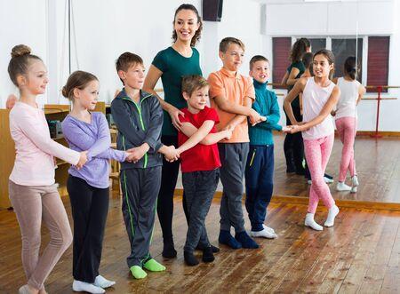 Glückliche positive Kinder tanzen Volkstanz im Studio, lächeln und haben Spaß