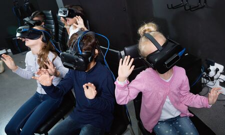 Enthusiastic happy positive smiling children in virtual reality glasses in quest room