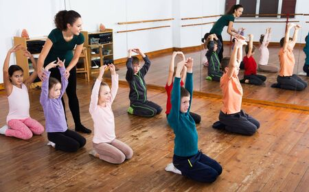 Little kids exercising with female teacher in dance class