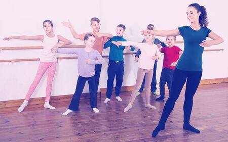 Group of positive american children practicing at the ballet barre
