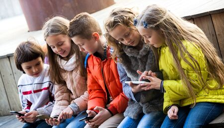 Outdoor portrait of little girls and boys playing with phones. Focus on the right