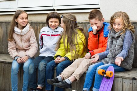 Group of happy positive children sitting on bench and sharing secrets outdoors