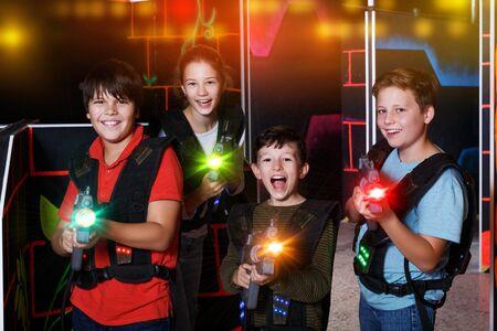Retrato de niños adolescentes emocionados felices con pistolas láser durante el juego de lasertag en una habitación oscura Foto de archivo