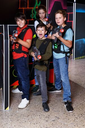 Smiling teen girl and boys with laser pistols posing together in dark laser tag labyrinth
