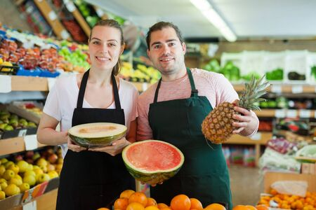 Young man and woman wearing aprons offering fresh fruits on the supermarket
