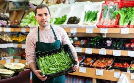 Young smiling glad friendly male seller standing with box of green beans on the supermarket Imagens