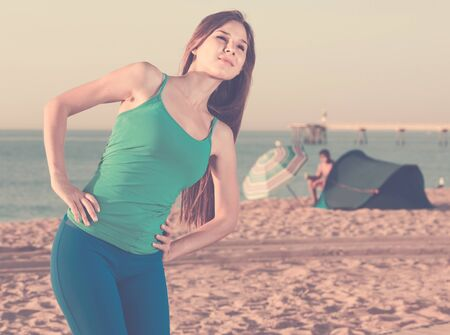 Female 20-25 years old is doing excercises for waring on the beach near sea. 스톡 콘텐츠