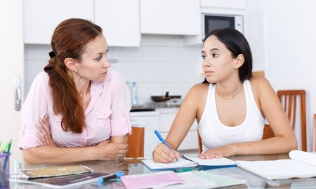 Mother and daughter in the kitchen, mother is not happy with grades of her daughter Standard-Bild