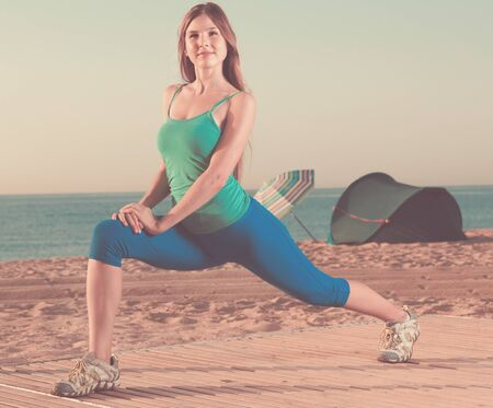Smiling young happy  woman in blue T-shirt is practicing stretching on the beach. 스톡 콘텐츠