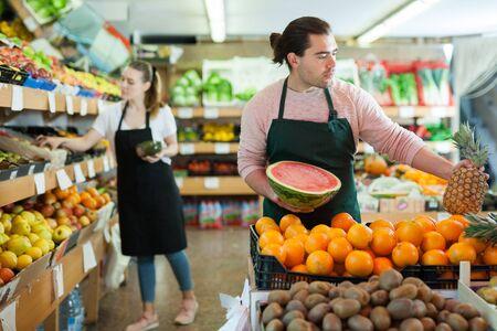 Jonge verkoper werkt met vers fruit in fruitwinkel, vrouw op achtergrond