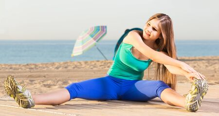 Smiling young glad beautiful woman in blue T-shirt is practicing stretching on the beach. Imagens