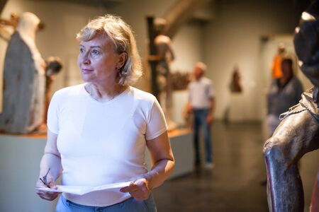 Mature woman holding brochure with information about exhibits on exposition of museum