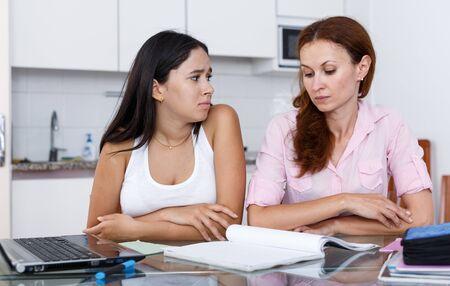 Mutter und Tochter in der Küche, Mutter ist mit den Noten ihrer Tochter nicht zufrieden