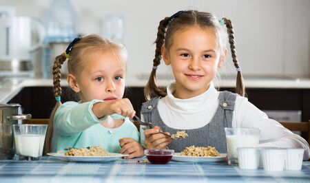 Portrait of happy little sisters with tasty porridge in kitchen Stock Photo