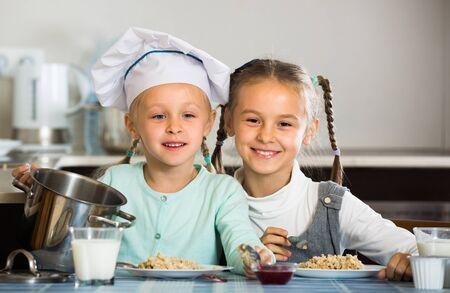 Portrait of happy smiling little sisters eating porridge in kitchen