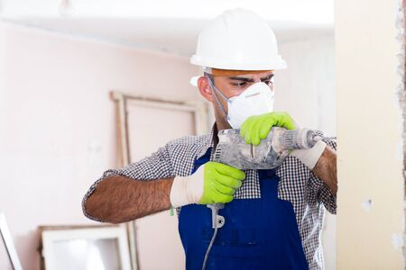 Man in helmet is perforating wall with drill in hands.