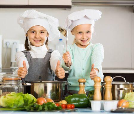 Dwie małe amerykańskie dziewczynki przygotowujące warzywa i uśmiechające się w pomieszczeniu