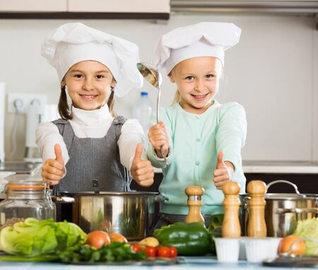 Two little american girls preparing vegetables and smiling indoors